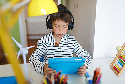 Boy doing homeschooling and using tablet and headphones at home - p300m2188718 by Epiximages