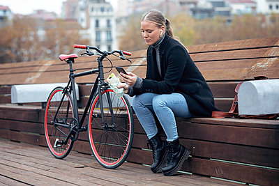 Woman using mobile phone while sitting on bench by bicycle - p300m2256045 by Josep Suria