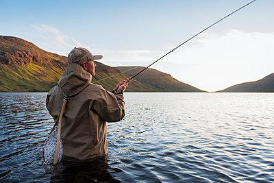 Man fishing in lake - p312m2051336 by Hans Berggren
