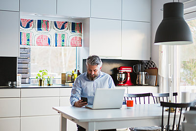 Man with laptop in kitchen - p352m1536605 by Calle Artmark