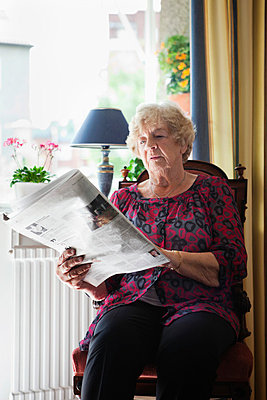 Relaxed senior woman reading newspaper at home - p4268993f by Maskot
