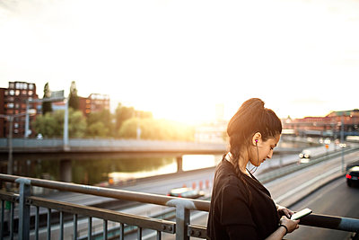 Side view of woman using mobile phone while on standing bridge against sky - p426m1212545 by Maskot