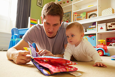 Mid adult man and baby daughter reading storybook in playroom - p429m1407951 by Emma Kim