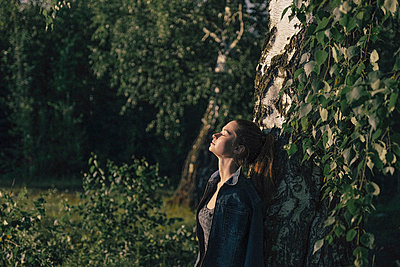 Caucasian woman leaning on tree trunk - p555m1531623 by Vladimir Serov