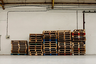 Stack of pallets in warehouse - p9241865 by Michael Swallow