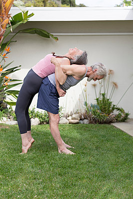 Senior couple in garden back to back doing resistance exercises - p924m1197095 by Alyson Aliano