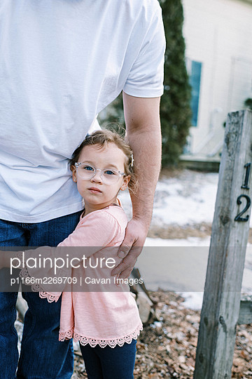 Little preschool aged girl with glasses holding on to her father - p1166m2269709 by Cavan Images