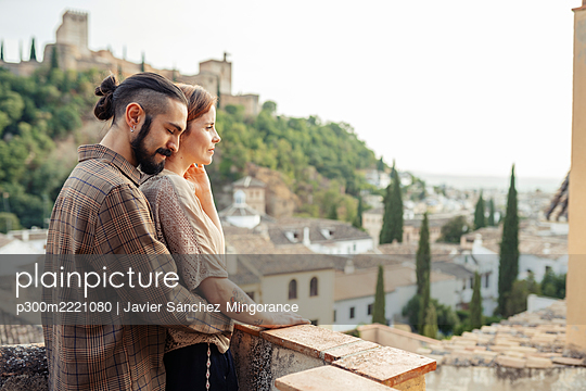 Man embracing woman from behind while standing on terrace - p300m2221080 by Javier Sánchez Mingorance