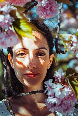 Frau schaut durch Kirschblütenzweige - p045m2027640 von Jasmin Sander