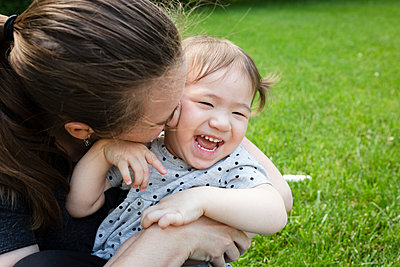 Happy Toddler Daughter Laughs As Mother Snuggles Her Closely - p1166m2218390 by Cavan Images