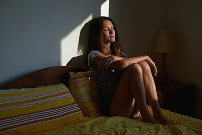 Woman sit on bed with her eyes closed in the bedroom - p1607m2181547 by zhushman