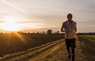 Man running in rural landscape at sunset - p300m1355959 by Uwe Umstätter