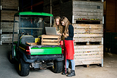 Two women using laptop between crates on a farm - p300m1563261 by Peter Scholl