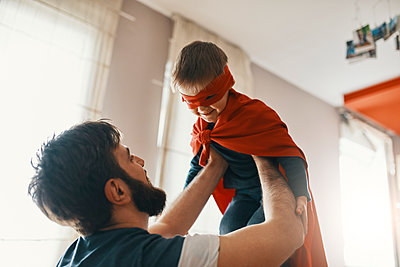 Father playing with his little son dressed up as a superhero - p300m1581701 by Zeljko Dangubic