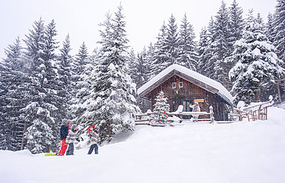 Austria, Altenmarkt-Zauchensee, family with sledges at wooden house at Christmas time - p300m2042011 by Hans Huber