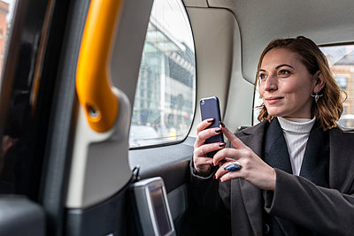Businesswoman in the rear of a taxi looking out of the window, London, UK - p300m2180785 by William Perugini