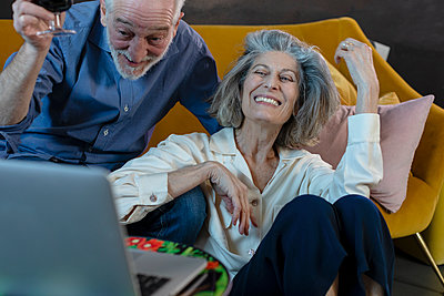 Happy man and woman smiling over video call on laptop at home - p300m2265124 by Emma Innocenti