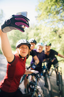 Young woman taking selfie with friends while mountain biking in forest - p426m2036675 by Katja Kircher