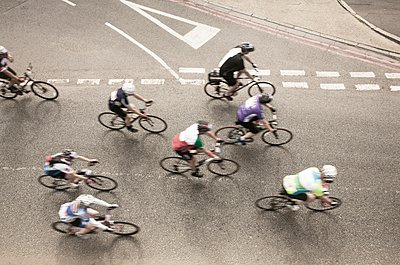 Overhead view of eight cyclists speeding on urban road in racing cycle race - p429m1118424f by Seb Oliver