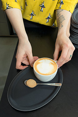 Hand of tattooed waitress serving cappuccino on cafe tray - p429m1135298f by Mischa Keijser