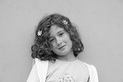 Smiling Young Girl with Two Flowers in Hair - p694m844290 by Julio Calvo