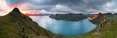 Panoramic of hikers on cliffs looking to the fjords, Funningur, Eysturoy island, Faroe Islands, Denmark - p871m2069082 by Roberto Moiola