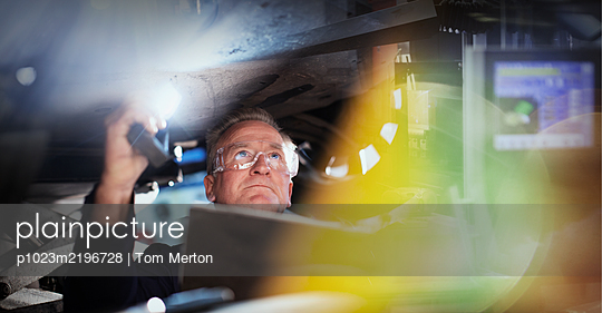 Focused male mechanic with flashlight under car in auto repair shop - p1023m2196728 by Tom Merton