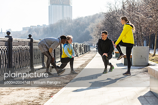 Friends doing stretching exercise on promenade in the city - p300m2004748 von William Perugini