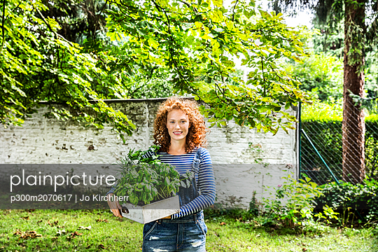 Portrait of young woman with fresh herbs in a box - p300m2070617 by Jo Kirchherr