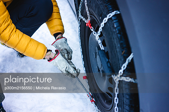 Man putting the snow chains on his car - p300m2156550 by Michela Ravasio