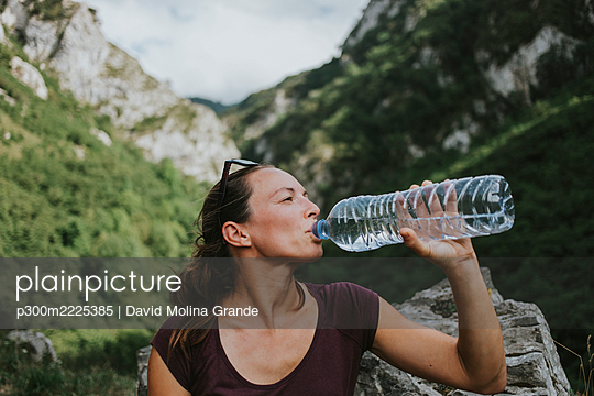 Mid adult female trekker drinking from plastic water bottle while looking away - p300m2225385 by David Molina Grande