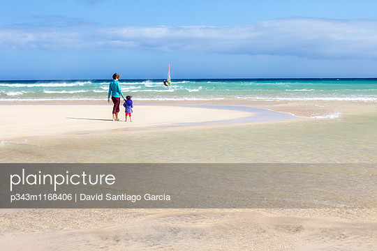 mother walking along an idyllic beach - p343m1168406 by David Santiago Garcia