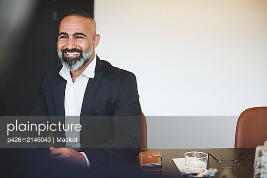 plainpicture - plainpicture p426m2146043 - Smiling confident lawyer si... - DEEPOL by plainpicture
