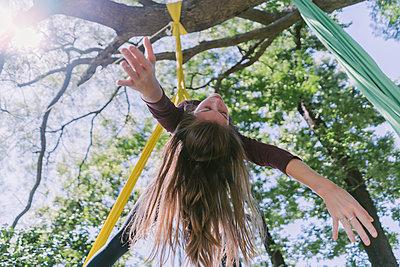 Acrobatic Girl Hanging On A Tree - p1166m2106795 by Cavan Images