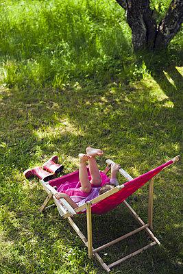 Little girl playing in deck chair - p1418m2002050 by Jan Håkan Dahlström