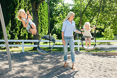 Mother with daughters on playground - p312m1229073 by Anna Rostrom