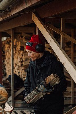 Woman holding firewood - p312m2191268 by Jennifer Nilsson