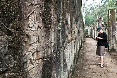 Woman traveller reading a guidebook at Angkor Wat, Cambodia - p3437166f by Thomas Pickard