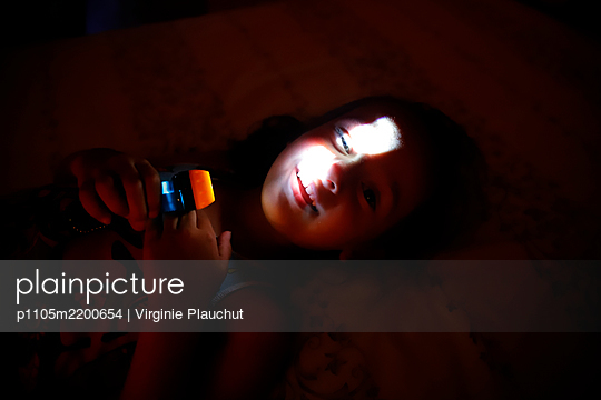 Little girl with flashlight - p1105m2200654 by Virginie Plauchut