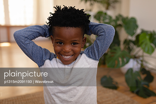 Happy cute boy standing with hands behind head at home - p1315m2091193 by Wavebreak
