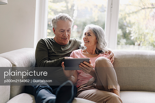 Happy senior couple relaxing on couch at home using tablet - p300m2154962 by Gustafsson