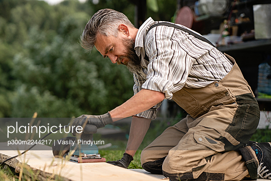 Carpenter grinding plank with hand grinder - p300m2244217 by Vasily Pindyurin