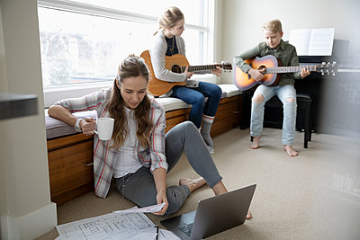 Mother working from home while children practice guitar in background - p1192m2088279 by Hero Images