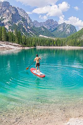 Man paddleboarding on turquoise Pragser Wildsee, Dolomites, Alto Adige, Italy - p300m2221230 by Michael Malorny