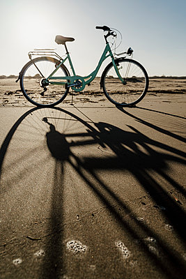 Bicycle with long shadow at Fangar Beach against clear sky, Ebro delta, Spain - p300m2250090 by VITTA GALLERY