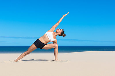 Woman on beach bending sideways arms raised in yoga position - p429m1494512 by Aziz Ary Neto