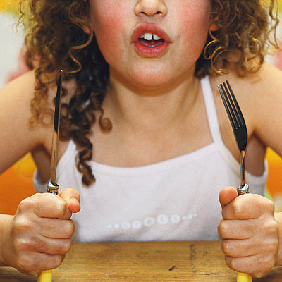 Girl holding up knife and fork - p6750033 by Mieke Dalle
