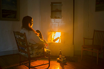 Young woman sitting by fire - p956m1044376 by Anna Quinn