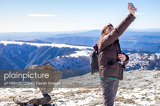 Young woman taking a selfie in the top of the mountain - p1166m2072064 by Cavan Images