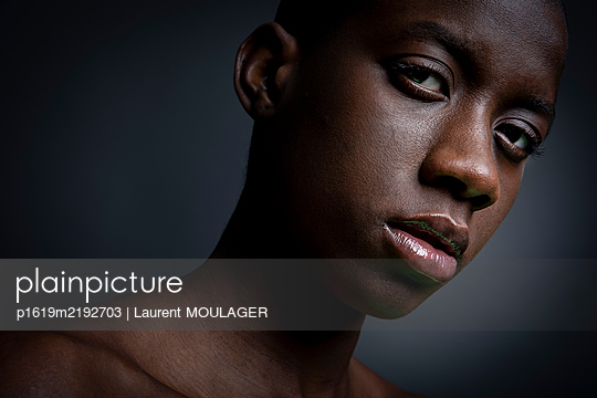 Portrait of a young black woman with shaved hair - p1619m2192703 by Laurent MOULAGER